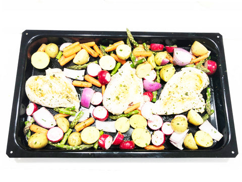 bake tray with uncooked veggies and chicken. ready for the oven