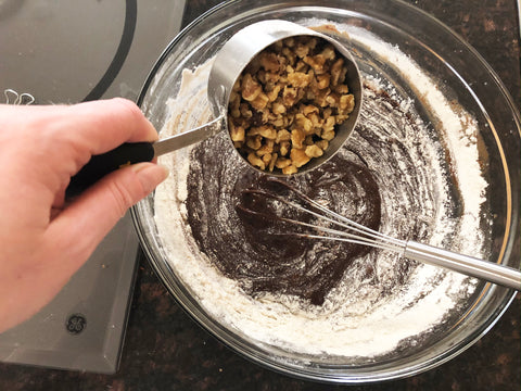 adding walnuts to mixing bowl for chocolate pie in deep dish pie dish