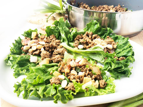 Plate of lettuce wraps with peanuts on top and ID21 coated saute