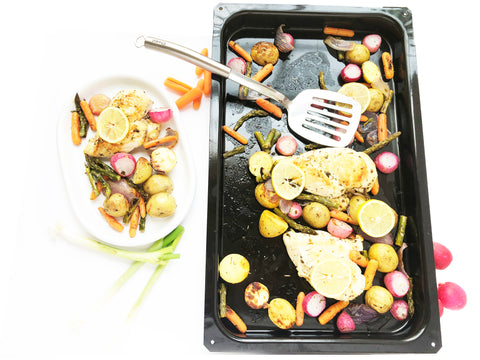 plate of chicken and vegetables radishes potatoes carrots onions and spatula enamel on steel bake tray