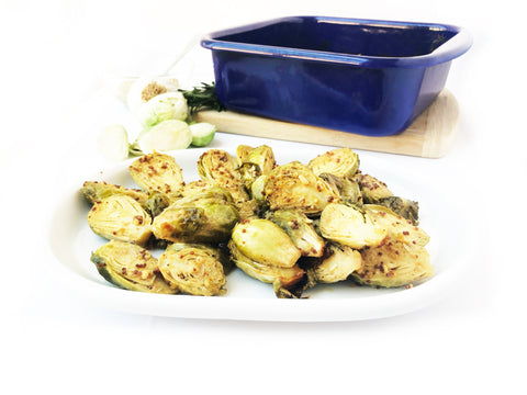 final brussel sprouts on plate with riess blue square oven dish in background