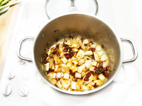 onions chipotle peppers and spices cooking in 6 qt stripes stock pot