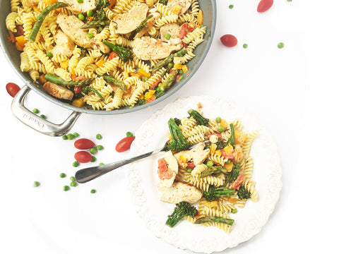 close up image of chicken pasta primavera plated and in 12 and a half inch ceramic coated fry pan