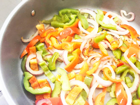 bell peppers and onions frying in 12 1/2 in induction 21 ceramic coated fry pan for bacon wrapped hot dogs recipe