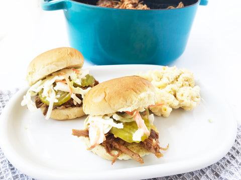 beer braised pork sliders plated with 7 quart blue dutch oven and lid