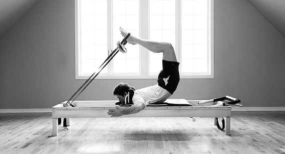 Gratz Gallery | Michael Johnson performing the Scorpion exercise on the Universal Reformer