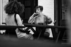 Two women having a conversation at a picnic table
