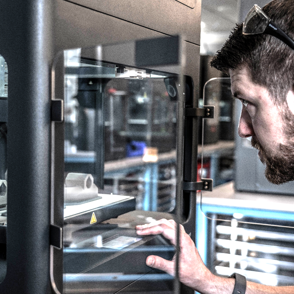 Additive engineer looking into viewing window of 3D printer