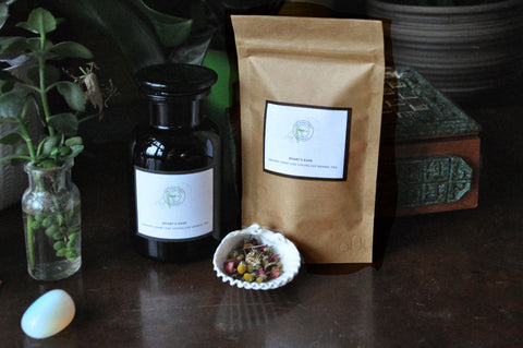 beautiful products from the modern witch apothecary in violet glass and eco pouches lined up on a dark wood table with plants and crystals featuring the relaxing loose leaf plastic free tea, Hearts Ease with rose camomile and lavender