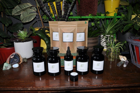 beautiful products from the modern witch apothecary in violet glass and eco pouches lined up on a dark wood table with plants and crystals