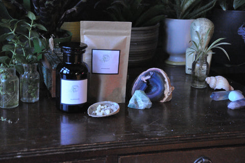 beautiful products from the modern witch apothecary in violet glass and eco pouches lined up on a dark wood table with plants and crystals featuring frankincense resin