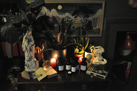 beautiful products from the modern witch apothecary in a night time candle lit scene with pictures, statues and objet d'art