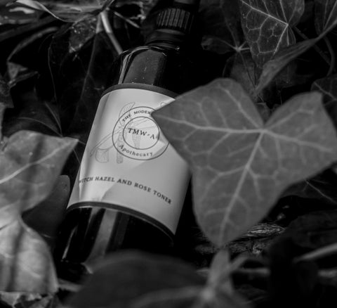 violet glass bottle of witch hazel and rose toner  in black and white with ivy plants