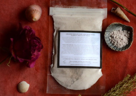 eco pouch filled with rose and clay organic powder face mask on red velvet with roses and seashells