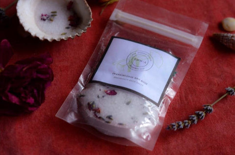 eco pouch of organic bath salts  on red velvet with roses and seashells