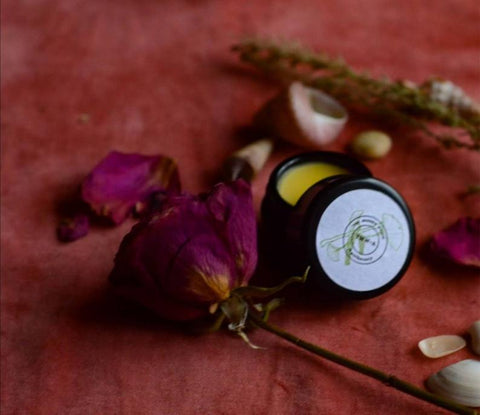 violet glass pot of super natural organic luxury lip balm on red velvet with roses and seashells