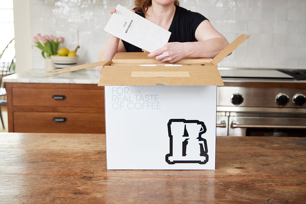 Person opening Moccamaster box and holding instruction manual