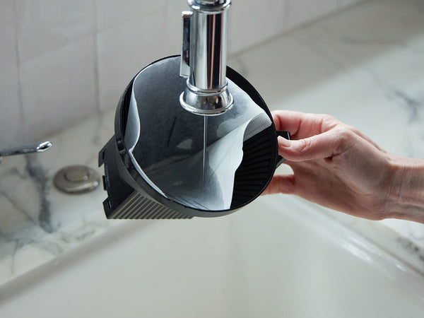 Rinsing coffee filter under the faucet