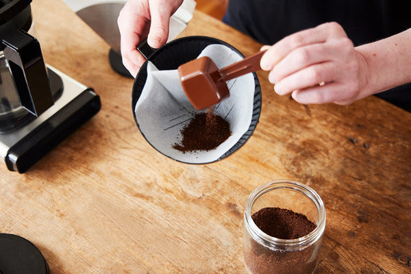 Scooping coffee grounds into the Moccamaster brew basket