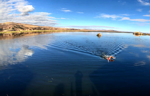 Open water swimmer swimming in Lake Titicaca Peru with the Andes in the background