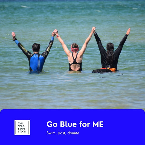 Three open water swimmers standing in the sea with their arms up for the ME Association wild swimming challenge