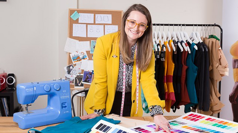 Rosie Cook - CEO and Founder of Sustainable Swimwear brand Deakin and Blue - stood by a table with her designs around her