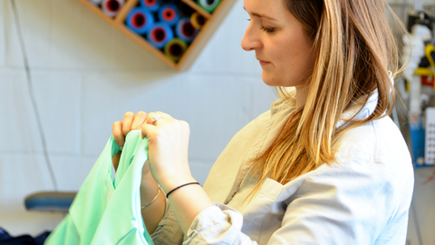 Rosie Cook CEO and Founder of Sustainable Wild Swim Swimsuits stitching a women's swimsuit