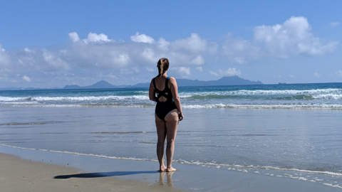 Rosie Cook from Deakin and Blue stood on the shoreline of a beach