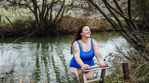 Cold Water Swimmer climbing out of a river wearing Deakin and Blue Sustainable Swimwear