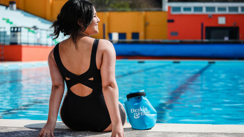 Lady sat on the edge of a lido outdoor swimming pool wearing a black swimsuit