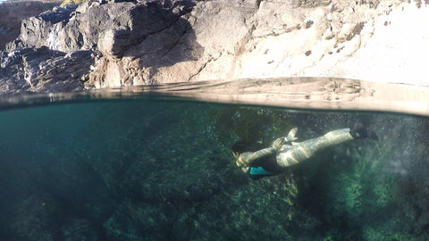 Photo of a swimmer diving underwater in a rock pool