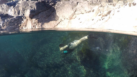 Open water swimmer diving under the sea in a rock pool