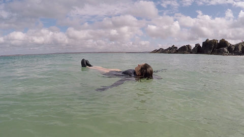 A swimmer lying on their back floating in the sea