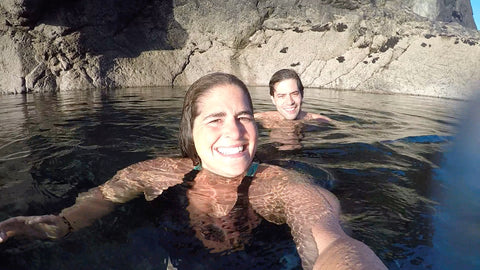 Photo of Tam and Jay in a tidal pool with the sun of their faces