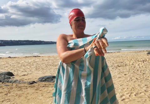 Wild Swimmer on a beach with beach towel and swim hat on