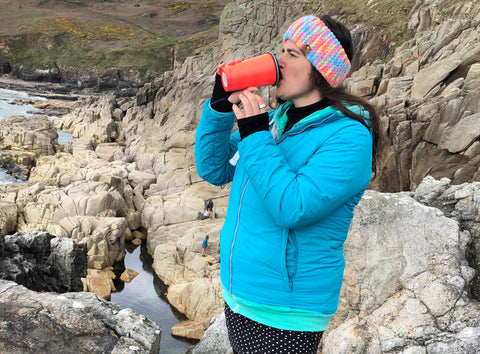 Cold Water Swimmer with hot drink post swim on the rocks in Cornwall