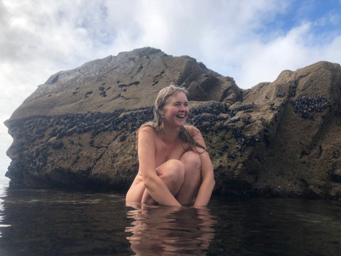Laura Evans the St Ives Mermaid sitting on a rock naked in a tidal pool