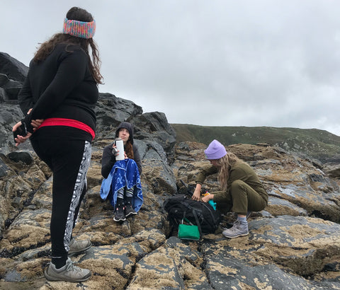 Group of women wild swimmers by a tidal pool in Cornwall