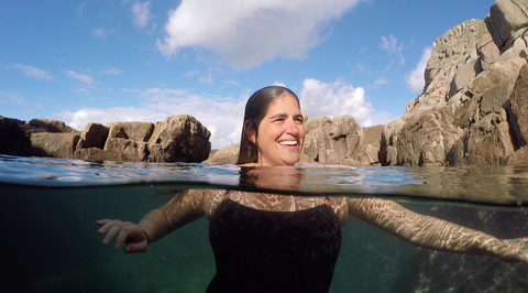 Outdoor swimmer in a tidal pool smiling