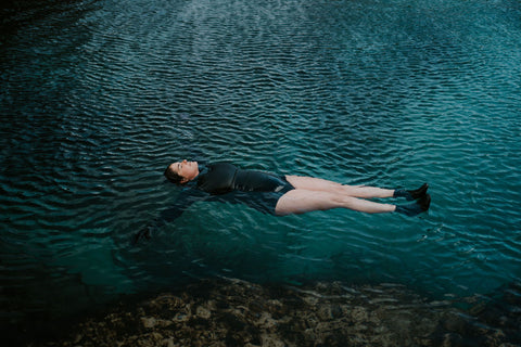 Wild swimmer floating on her back in a tidal pool