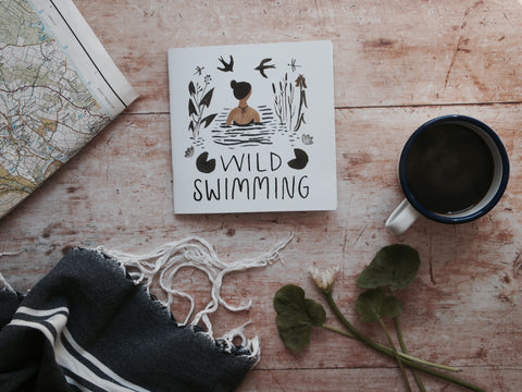A table with The Little Wild Swimming Book on it and a cup of coffee, hammam towel, leaves and ordnance survey map
