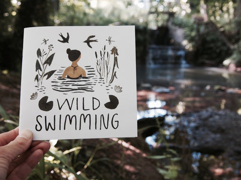 The Little Wild Swimming Book held up in front of a wild swimming spot