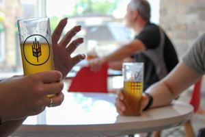 two glasses of beer being held by hands on a table at bitte schon brauhaus the cans contain craft beer made in ontario