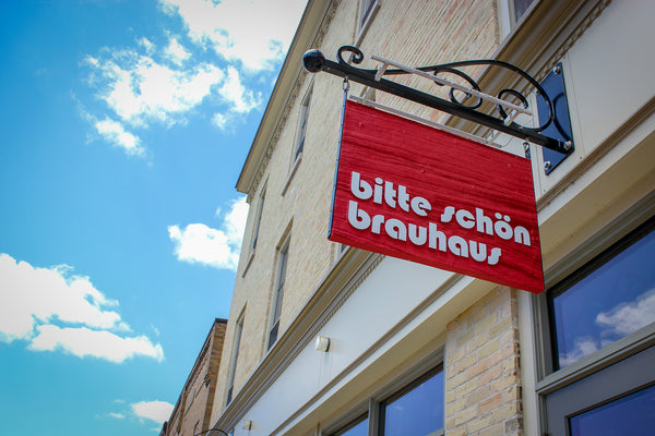 a blue sky with a red sign that says bitte schon brauhaus the sign is outside of our craft brewery located in new hamburg ontario