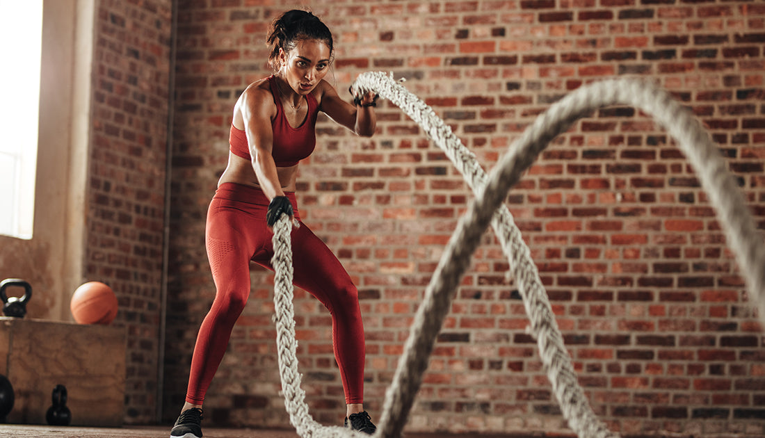 beautiful in shape woman battle rope fat loss