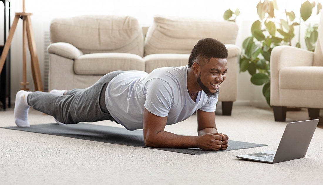 healthy happy african american man doing exercise planks at home for abs and core strength