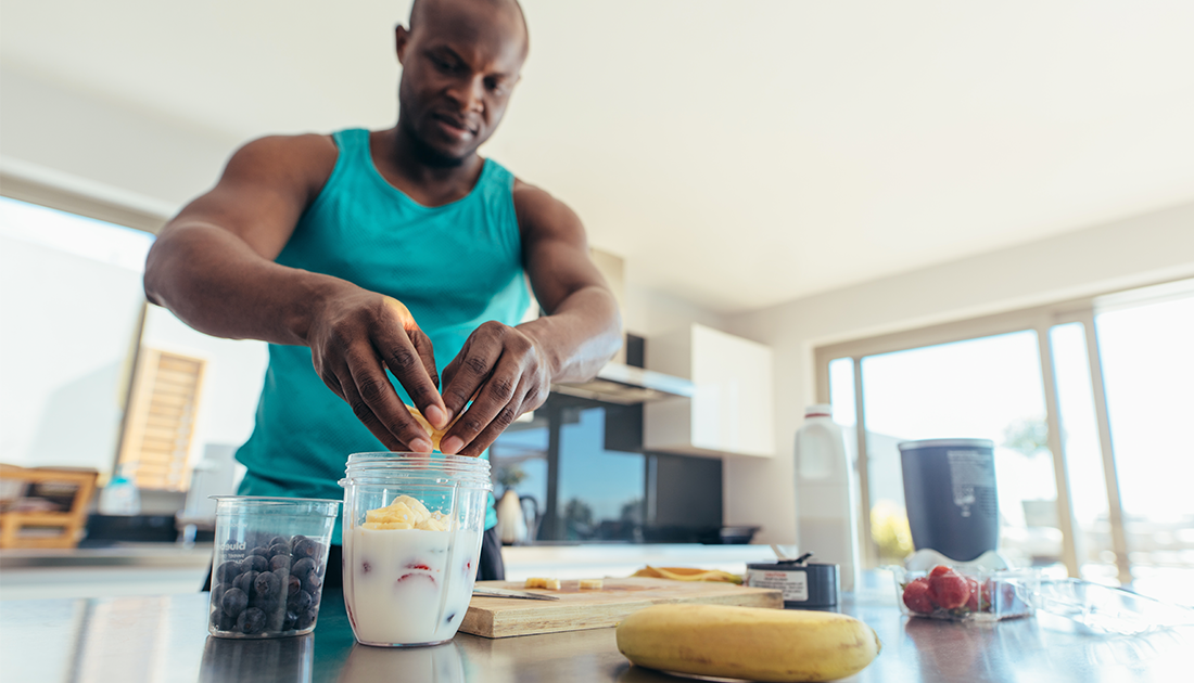 Muscular man putting chopped bananas into protein shake