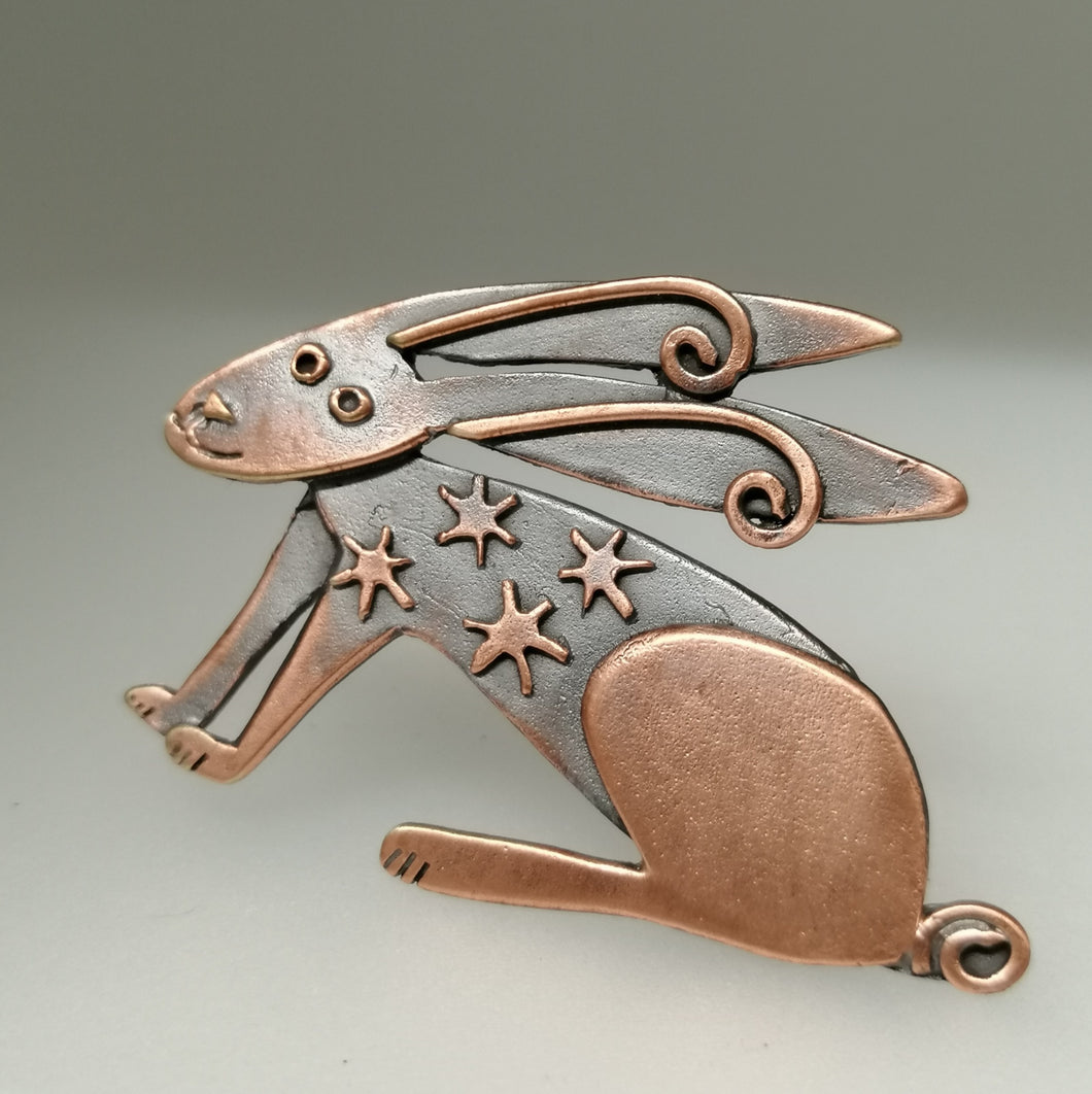 Copper coloured hare brooch with stars on its body handmade by Sharon McSwiney