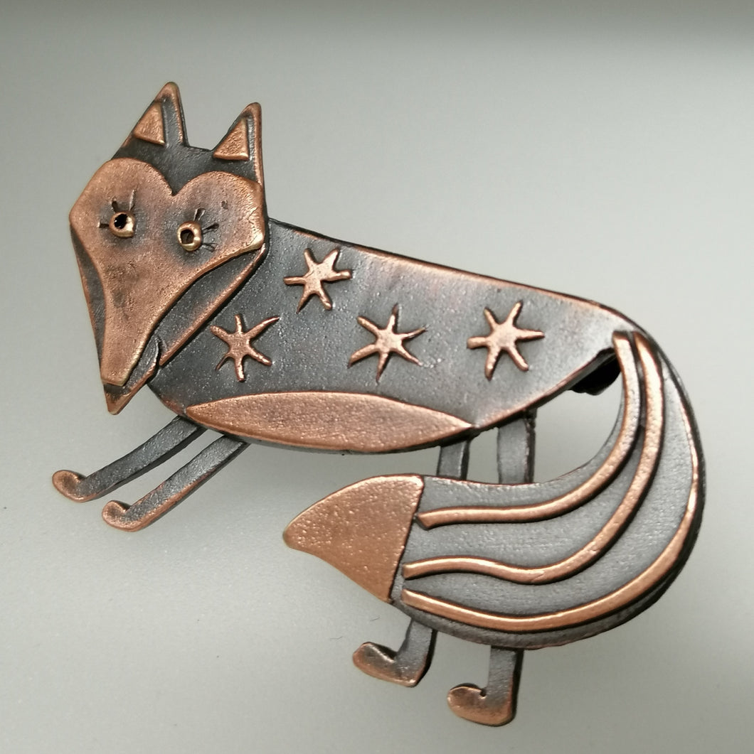 Fox brooch with stars on its body in a copper finish handmade by Sharon McSwiney