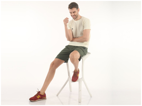 man sitting on a chair wearing almo t-shirt and green almo shorts